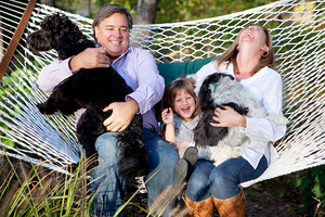 mom dad daughter laughing on the hammock with dogs