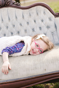 little girl with pink glasses lying on couch