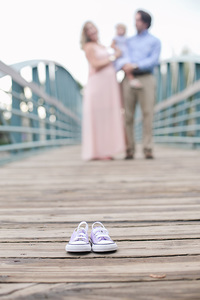 baby shoes and family on bridge
