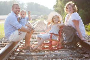 family sitting on train tracks