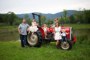 family in front of red tractor