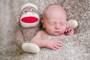 newborn with sock monkey