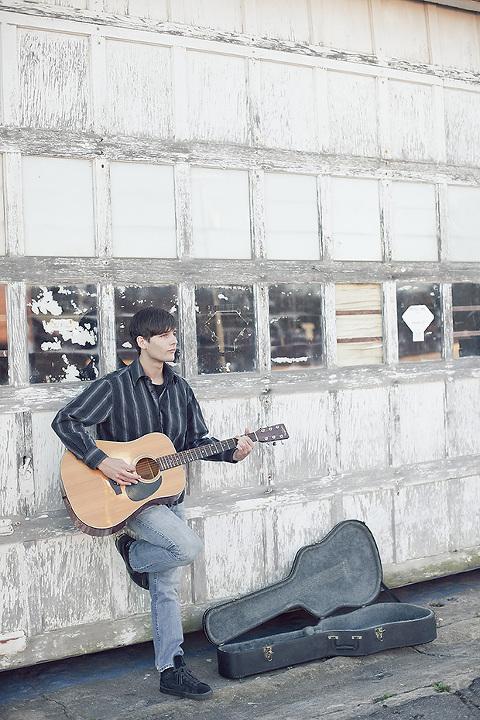 boy playing guitar in front of garage door