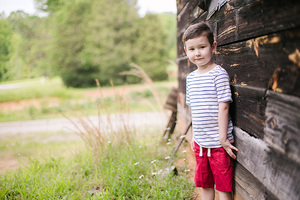 boy next to old barn
