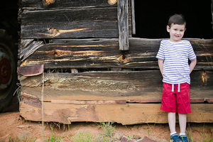 boy next to old house