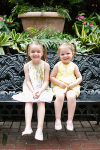 Sweet girls sitting on the bench in the Conservatory at Biltmore Estate for their Family Photo Session