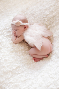 newborn baby girl with headband and angel wings on white blanket