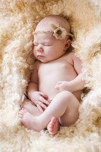 newborn with headband snuggled in sheepskin